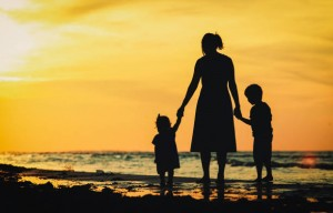 mother and two little kids walking on beach at sunset